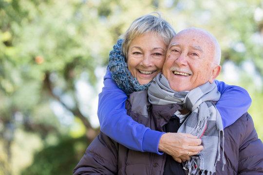 Coppia di anziani si abbraccia felici su sfondo parco
