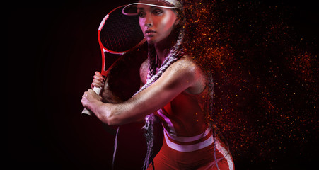 Tennis player. Beautiful woman athlete with racket in red costume and hat isolated on black background. Fashion and sport concept.