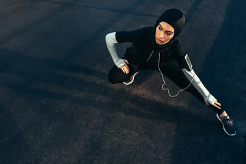 Woman wearing Muslimah sportswear stretching outdoors
