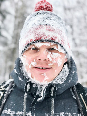 Close up portrait of man with frozen snowy face and hat