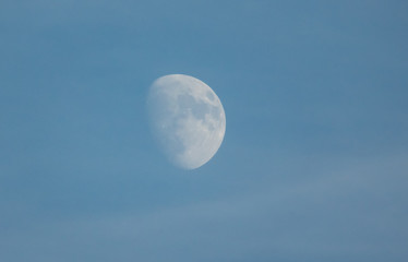 Half moon on daylight blue sky.
