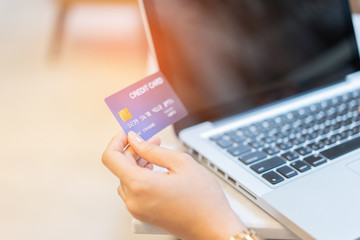 Asian Woman's hands holding a credit card and using smart phone and laptop tablets for online shopping,she smiling ,looking her credit-card shop Online payment and retail concept,Internet Theft alert