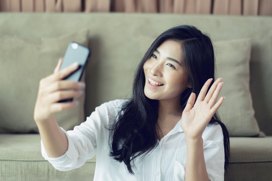 Selfie mania! Excited,Young attractive Asian woman making selfie on a smartphone camera or recording video vlog on a mobile phone. popular vlogger smiling to followers communicating by webcam online