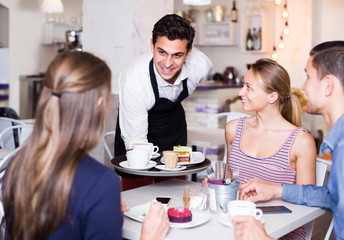cheerful waiter bringing ordered dishes to friends in tearoom