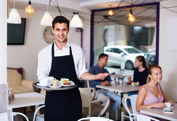 Waiter holding served tray meeting visitors at pastry bar
