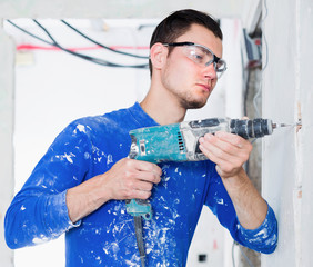 Portrait of young handyman using electric drill