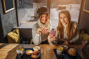 Positive young women take selfie. Blonde model hold phone in hand. They pose. There are food at table. Sun shines outside.