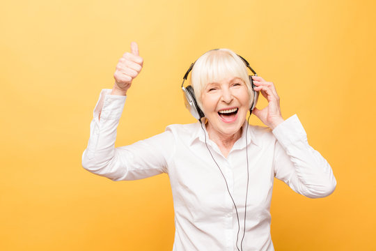 Elderly cheerful woman with headphones listening to music on a phone and dancing isolated on yellow background. Thumbs up.