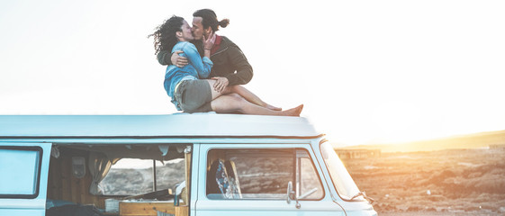 Happy travel influencers couple kissing on minivan roof at sunset with desert on background