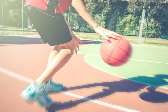 teenager play basketball outdoor - healthy sporty teenagers lifestyle concept in spring or summer time