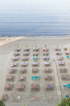 Aerial view to sandy beach of Adriatic sea in Albania, full of umbrellas and sunbeds, Port of Durres in horizon..