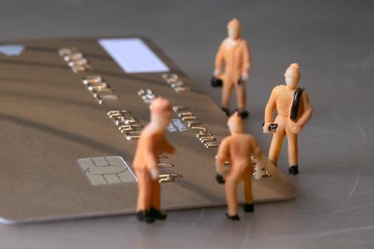 Mini workers repair one golden credit card
