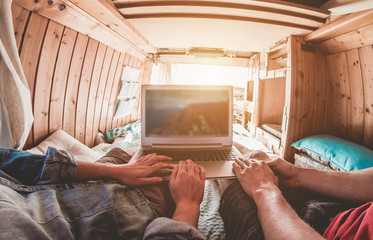 Digital nomad couple working inside minivan with wood interiors