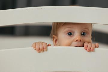 portrait of cute little baby boy peeking from cot