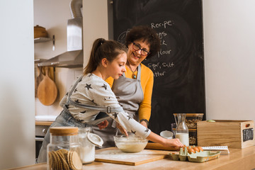 kitchen is the heart of the home. grandma with her granddaughter baking together in kitchen