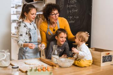 senior woman with her grandchildren baking together in kitchen