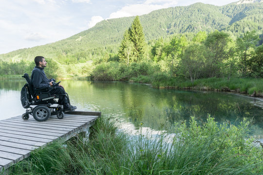 Disabled man on wheelchair enjoying and looking at beautiful nature on lake pier