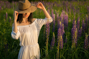 young pretty sexy girl in a woman's crimson wicker hat and in a white long dress standing at sunset on the field of lupine and fixing the hat with her hand