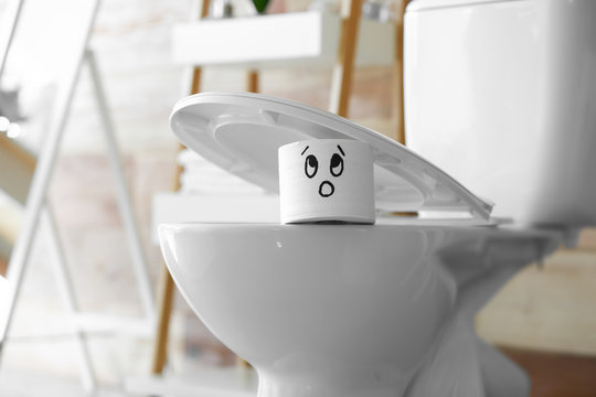 Roll of paper with funny drawn face under seat of toilet bowl