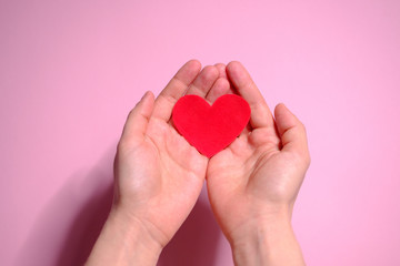 Heart in hands on a pink background. Valentine's Day