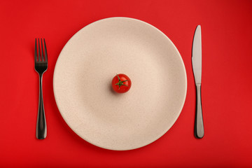 Plate with one tomato and cutlery on color background. Diet concept