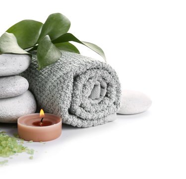 Beautiful spa composition with stones, towel and candle on white background