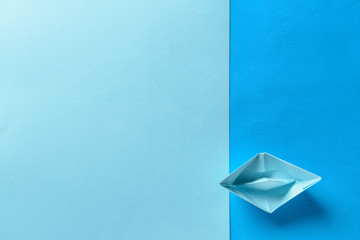Origami boat on color background