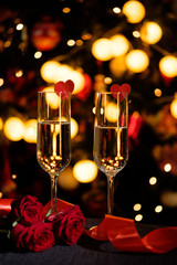 Glasses of champagne on the background of lights with roses and red ribbon
