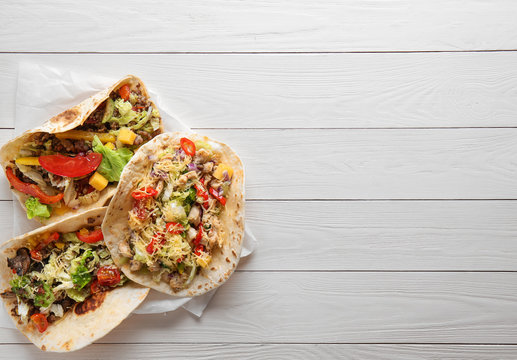 Tasty tacos on white wooden table