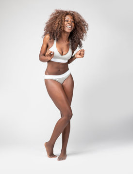 Happy beautiful African American Girl with wild curly hair and wearing underwear in studio with a gray background