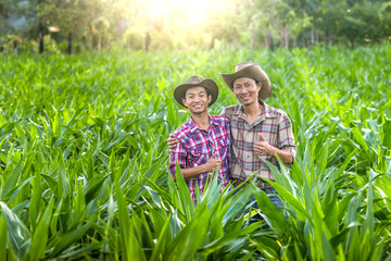 Two farmer smiling and hugging each other in corn field.