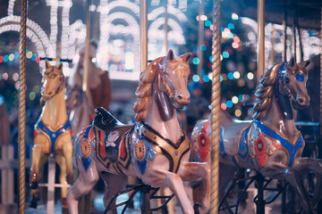 A young woman rides a merry-go-round with horses at the New Year's Fair
