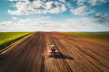 Farmer with tractor seeding crops at field, aerial view Wall mural