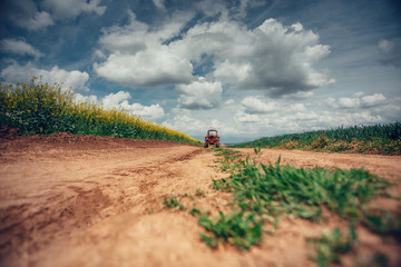 Wall Mural - tractor in a field and dramatic clouds