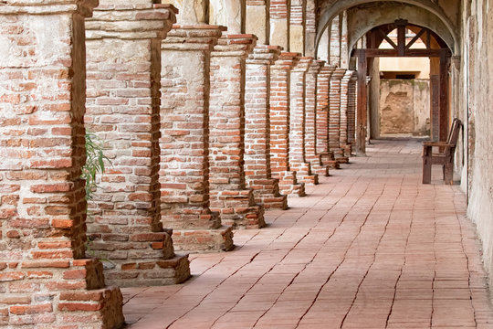 Photograph of an old arched brick walkway with brick pillars