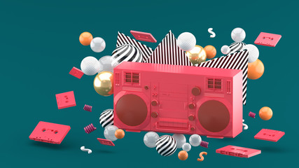 Red radio amidst colorful balls on a green background.-3d render..
