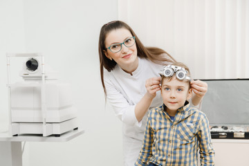 Young girl doctor holding up patient special glasses for eye tests and selection of lenses. Little beautiful blonde boy