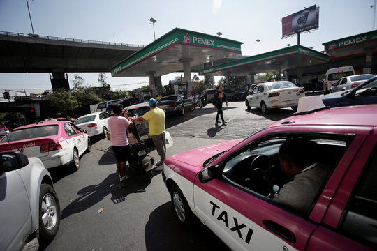 Cars are seen lined-up to buy fuel at a gas station in Mexico City