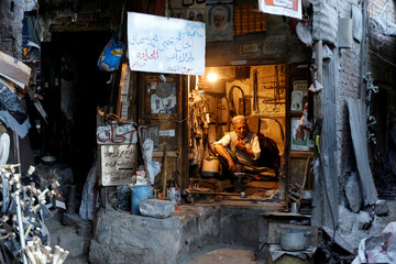 A blacksmith sits in his shop at the Souq al-Melh market in the old quarter of Sanaa