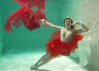 Hot Slim Caucasian Woman Posing Under water in beautiful clothes alone in the deep