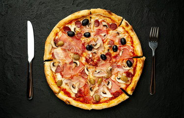 Tasty pizza on black concrete  background.