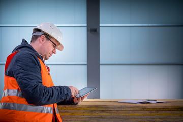Portrait of development supervisor wearing protective vest and helmet proofing blueprints using a digital tablet inside unfinished building