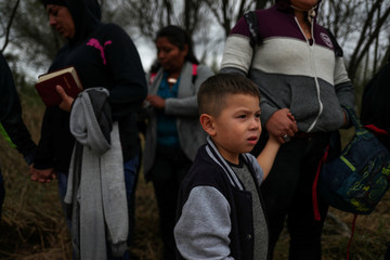 Migrant boy from Honduras holds the hand of his mother after illegally crossing into the U.S. from Mexico in Penitas, Texas