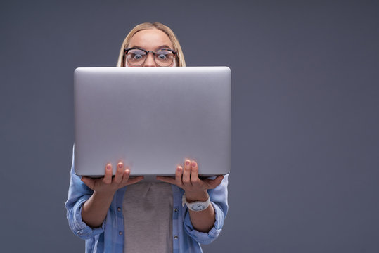 Beautiful young lady hiding behind silver laptop