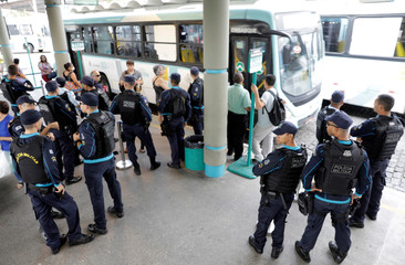 Police officers patrol a bus terminal in Fortaleza, Brazil