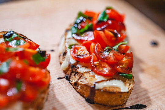 Traditional Italian bruschetta with cherry tomatoes, cheese, basil and balsamic vinegar on wooden board. Close up