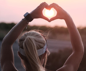 female making a heart sign with her hands for Valentines with sun in the middle