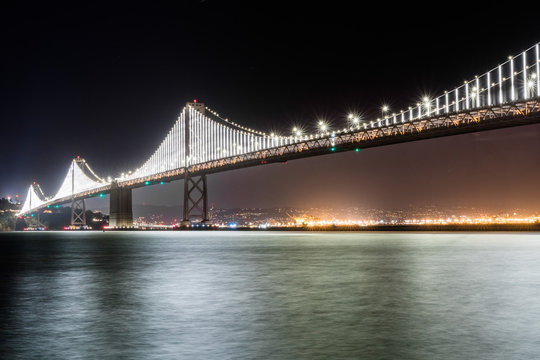 The illuminated Bay Bridge connecting San Francisco and Oakland via Treasure island on a clear night' long exposure; San Francisco bay area, California