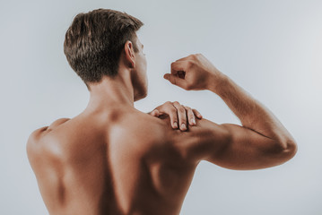 Close up of muscular man touching shoulder and banding elbow Wall mural