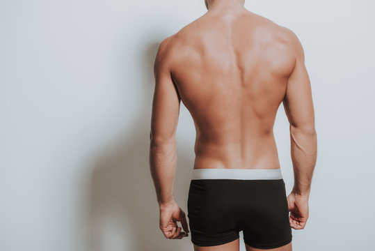 Back of young caucasian man standing in black underwear